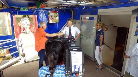 Die Unterwegs-Moderatoren Victoria Herrmann und Andreas Neugeboren werden an Board eines Schiffes begrüßt und dabei gefilmt