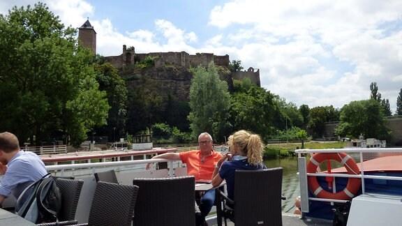 Die Unterwegs-Moderatoren Victoria Herrmann und Andreas Neugeboren sitzen an Deck eines Schiffes, im Hintergrund ist die Burg Giebichenstein zu sehen