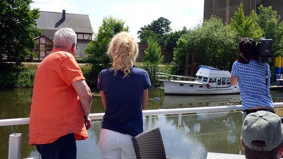 Die Unterwegs-Moderatoren Victoria Herrmann und Andreas Neugeboren und eine Kamerafrau stehen an Deck eines Schiffes und schauen Richtung Ufer mit Häusern
