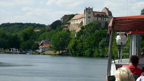 Schiff mit Passagieren auf der Saale fährt an Burg in Wettin entlang