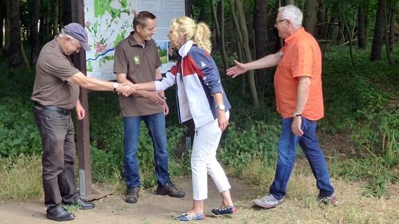 Die Unterwegs-Moderatoren Victoria Herrmann und Andreas Neugeboren begrüßen zwei Männer, die an einem Schild im Wald stehen