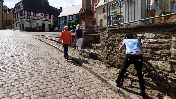 Die Unterwegs-Moderatoren Victoria Herrmann und Andreas Neugeboren gehen durch die gepflasterten Straßen von Wettin und werden dabei gefilmt