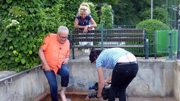 Unterwegs-Moderator Andreas Neugeboren wird beim Wassertreten von Kamerafrau gefilmt, Victoria Herrmann schaut zu