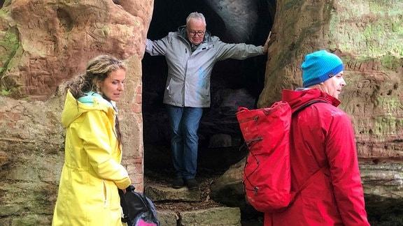 Victoria Herrmann und Andreas Neugeboren und ein Mann am Eingang einer Höhle