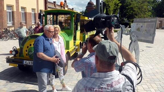 Victoria Herrmann und Andreas Neugeboren stehen vor kleiner Bahn und werden von Kamerateam gefilmt