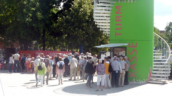 Menschentraube steht vor einem grünen Kassen-Turm