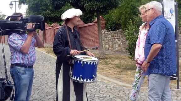 Victoria Herrmann und Andreas Neugeboren sprechen mit Trommler und werden dabei gefilmt