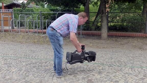 Kameramann filmt gebückt etwas auf einem Gehweg