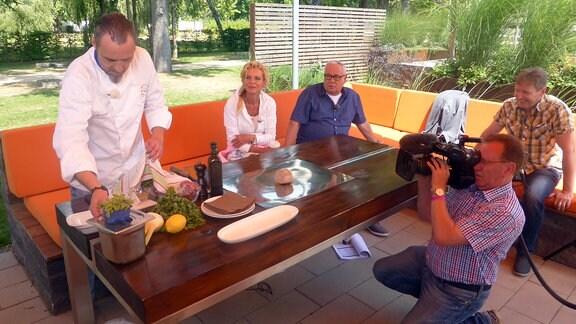 Victoria Herrmann und Andreas Neugeboren sitzen an Tisch mit einem Koch, der Essen zubereiten will, dabei werden sie gefilmt
