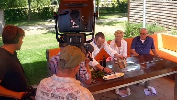 Victoria Herrmann und Andreas Neugeboren sitzen an Tisch mit einem Koch, der Essen zubereitet, dabei werden sie von Kamerateam gefilmt