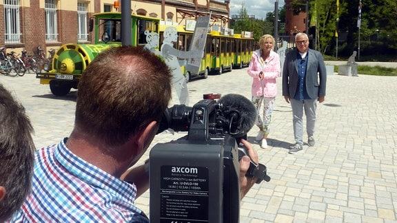 Victoria Herrmann und Andreas Neugeboren laufen an einer kleinen Bahn vorbei und werden dabei gefilmt
