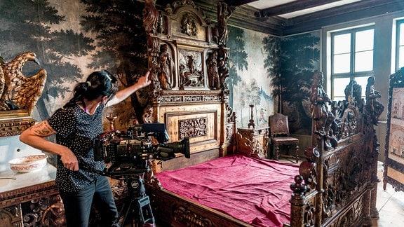 Dreharbeiten in historischem Schlafzimmer mit altem Holzbett.