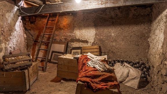 Kellerraum mit alten Kisten und Bildern.