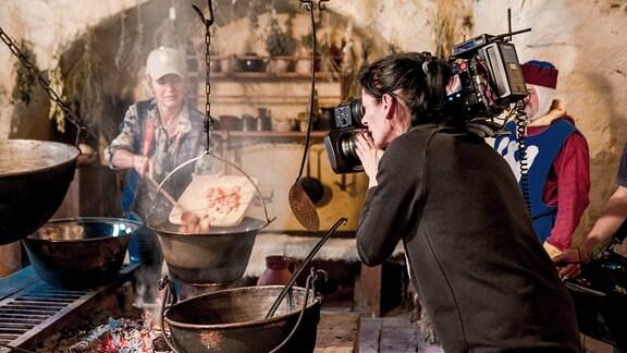 Dreharbeiten in historischer Küche mit Töpfen über offenem Feuer.