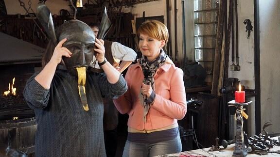Redakteurin Kerstin Mempel (hinter Maske) erklärt Beate Werner, wie scharfzüngige Damen im Mittelalter korrekt eine Schandmaske tragen mussten