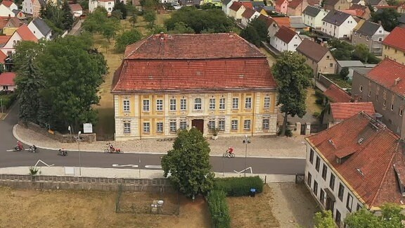 Blick von oben auf ein gelbes Haus umgeben von einer Straßen und weiteren Häusern.
