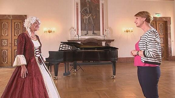 Zwei Frauen (linksstehend in Kostüm) stehen sich in einem alt erscheinendem Saal gegenüber.