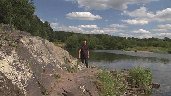 Ein Mann steht an einem Stein neben einem See.