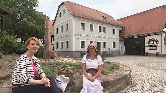 Zwei Frauen (rechts in Kostüm) sitzen auf einem Stein vor einem historischen Haus.