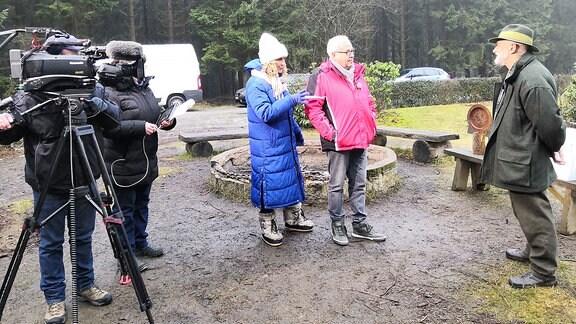 Die Moderatoren Victoria Herrmann und Andreas Neugeboren werden auf Rastplatz im Wald gefilmt.