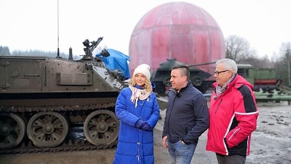 Victoria Herrmann und Andreas Neugeboren im Gespräch vor einem Panzer und einer großen Kuppel.