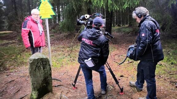 Andreas Neugeboren steht an einer Markierung im Wald und wird gefilmt