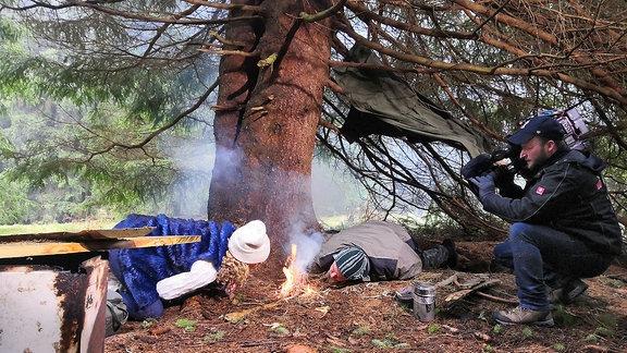 Victoria Herrmann und ein Mann machen ein Feuer im Wald und werden gefilmt
