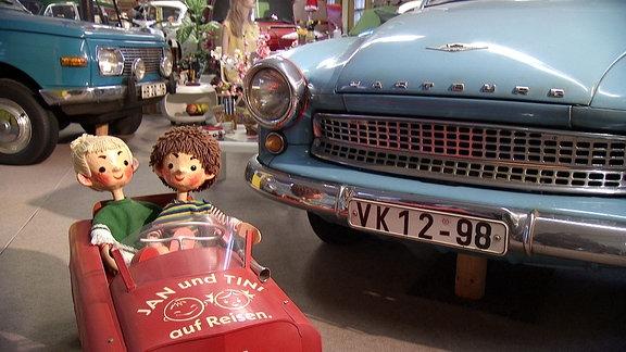 DDR-Spielfiguren und Oldtimer in einem Museum.