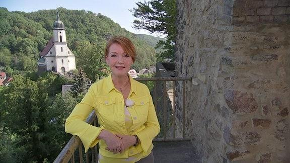Beate Werner steht auf der Burg Tharandt und schaut lächelnd in die Kamera.