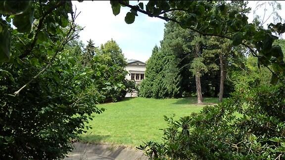 Ein teilweise von Bäumen verdecktes, herrschaftliches Anwesen in einem Park