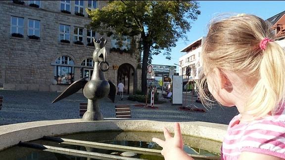 Ein blondes Mädchen mit einem Pferdeschwanz blickt auf eine Metallskulptur auf einem Brunnen, die einen Vogel mit Krone und Ring im Schnabel darstellt