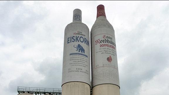 Zwei Türme auf einem Industriegelände einer Brennerei stellen Schnapsflaschen dar