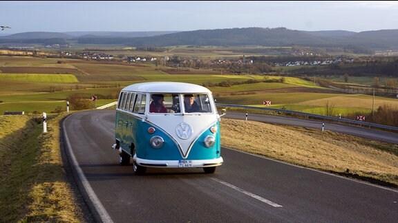 Ein alter VW-Bus fährt auf einer Asphaltstraße durch eine hügelige Landschaft