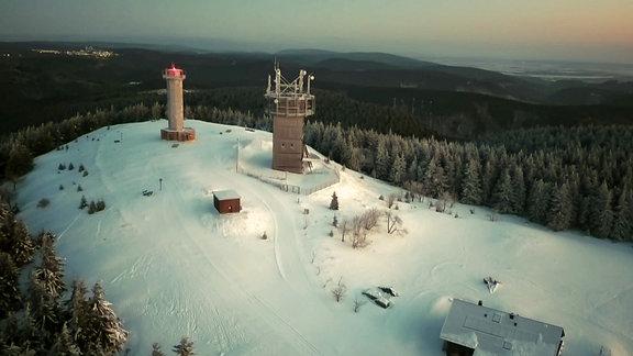 Spitze des Schneekopfes mit Aussichtsturm und umliegenden Wald im Abendlicht.