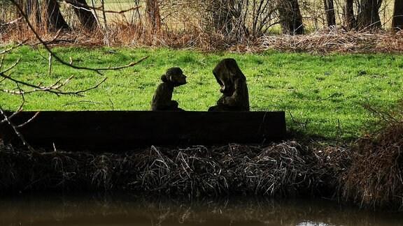 An einem Fluss steht eine Skulptur. Sie zeigt ein Boot, in dem zwei Menschen sitzen