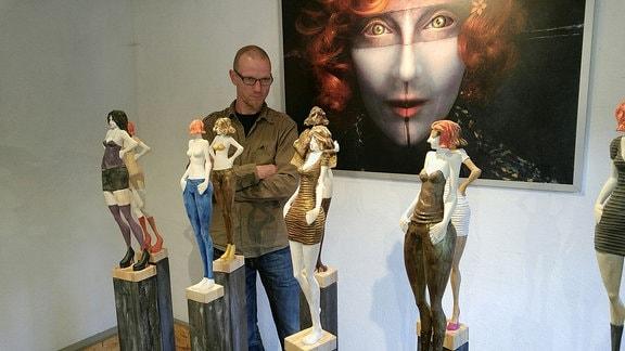 """Bildhauer Stefan Neidhardt steht neben seinen Plastiken für die Ausstellung """"Die Waffen der Frauen"""" im Suhler Waffenmuseum."""