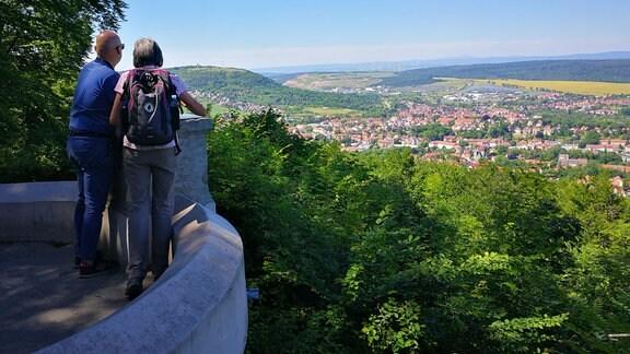 zwei Personen stehen an einem Aussichtspunkt und schauen auf einen Ort
