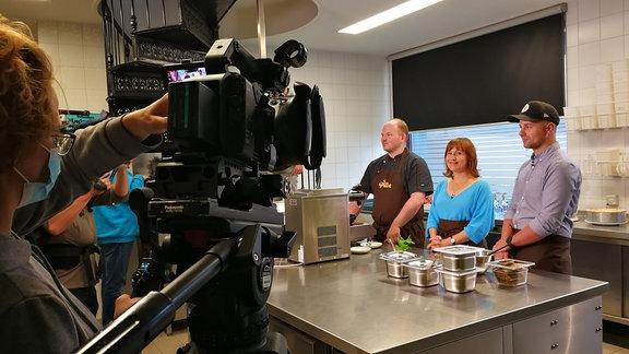 Ein Fernsehteam filmt drei Personen in einer Küche