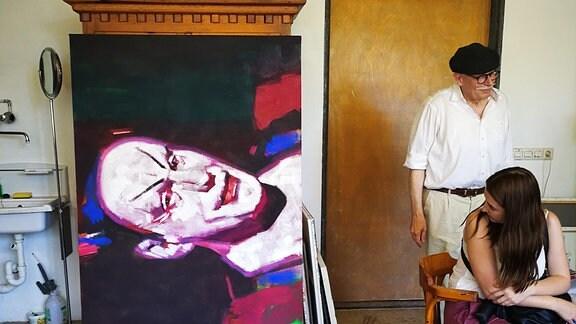 Zwei Personen neben einem großen Gemälde in einem Atelier