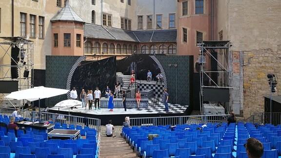 Ein Theaterstück auf einer Bühne vor einem Schloss. Vor der Bühne befindet sich eine große Zuschauertribüne
