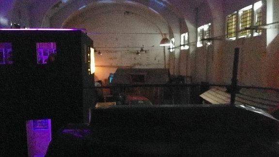 In einer alten Halle sind vereinzelt bunte Lichter an. Es handelt sich um eine Lasergame-Arena.