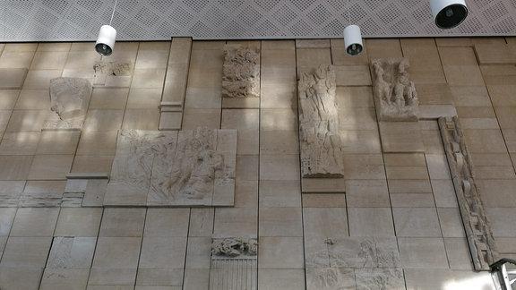 Eine Wand besteht aus in Steinplatten geschlagenen Kunstwerken.