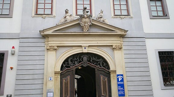 Eine größe Eingangstür führt in den Innenhof eines Hauses. Die Fenster sind mit Stuckreliefs verziert.