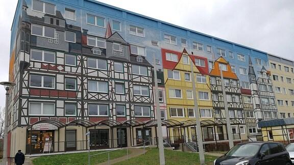 Auf einem Plattenbau sind künstlerisch Fachwerkhäuser angemalt. Es entsteht die Illusion, dass dort Fachwerkhäuser vor einem blauen Himmel stehen.
