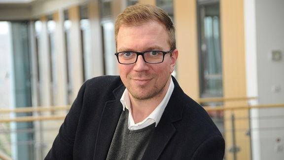 Mann kurzem blonden Haar und schwarzer Brille schaut in die Kamera.