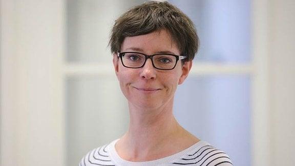 Frau mit kürzeren Haaren und Brille