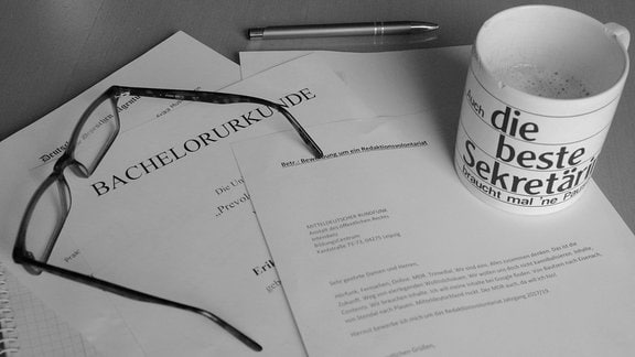 Auf einem Tisch liegen Unterlagen für eine Bewerbung. Darauf steht eine Kaffeetasse.