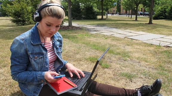 Eine junge Frau sitzt mit Laptop, Kopfhörern und Smartphone auf dem Rasen