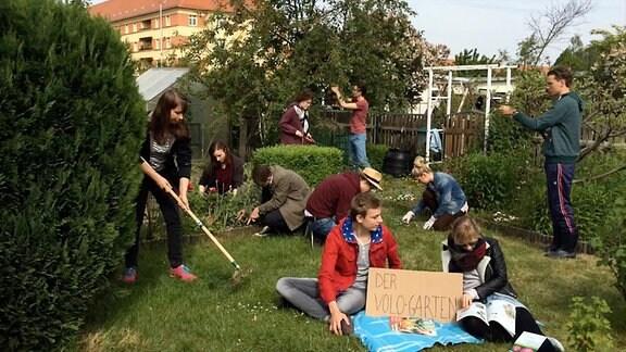 Gruppe von jungen menschen arbeitet in einem Schrebergarten