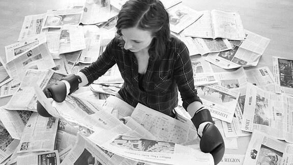 Eine junge Frau hat um sich zahlreiche Zeitungen ausgebreitet. Sie trägt Boxhandschuhe und liest in einer Zeitung.